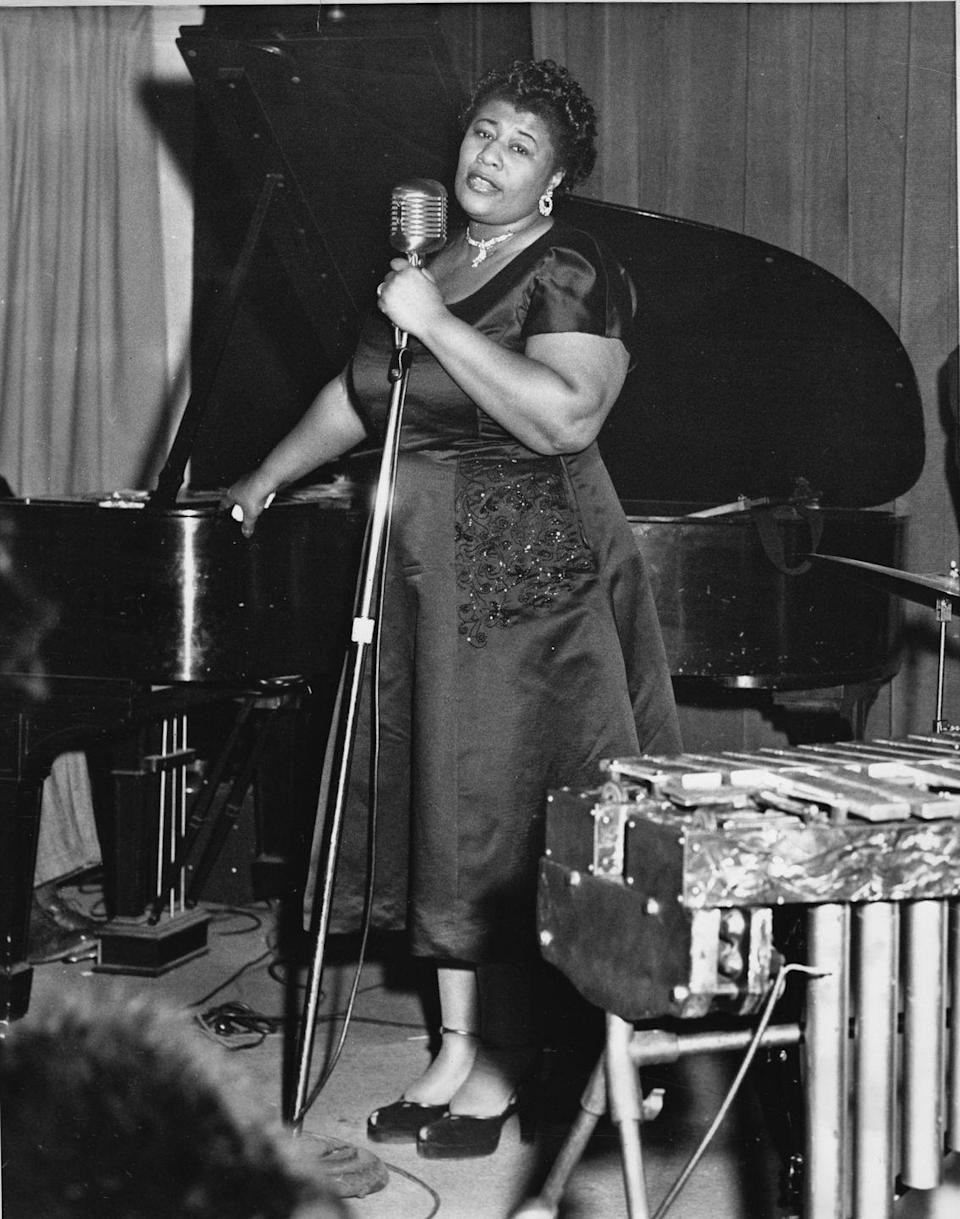<p>Ella Fitzgerald performing in an all-black duchess satin dress with platform patent-leather Mary Janes.</p>