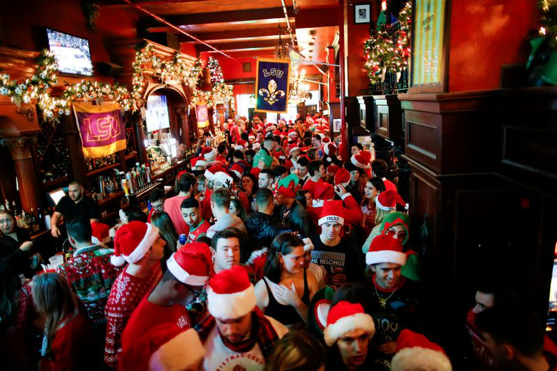 FILE PHOTO: Revelers dressed as Santa Claus share drinks in a local bar as they take part in the event called SantaCon in New York
