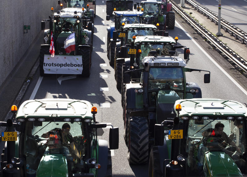 "Protesting farmers on tractors, one with a sign reading ""Proud of the Farmer"", block a main road leading to the center of The Hague, Netherlands, Wednesday, Oct. 16, 2019. Thousands of Dutch farmers protest over the Netherlands efforts to drastically reduce emissions of greenhouse gases. Among the farmers' demands are that the government does not further reduce the number of animals they can keep. (AP Photo/Peter Dejong)"