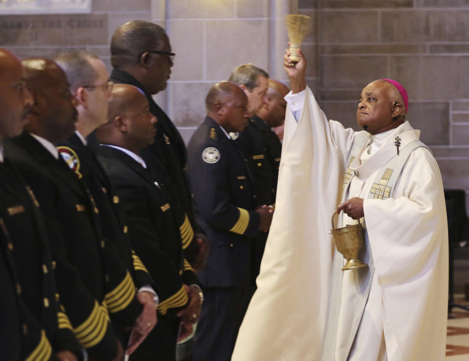 """FILE - In this Sept. 11, 2015, file photo, Archbishop Wilton Gregory, right, celebrates mass and blesses the badges of the first responders as the Archdiocese of Atlanta held its first """"Blue Mass"""" for public safety officials and first responders in Atlanta. Pope Francis on Sunday, Oct. 23, 2020, named 13 new cardinals, including Washington D.C. Archbishop Wilton Gregory, who would become the first Black U.S. prelate to earn the coveted red hat. In a surprise announcement from his studio window to faithful standing below in St. Peter's Square, Francis said the churchmen would be elevated to a cardinal's rank in a ceremony on Nov. 28. (Bob Andres/Atlanta Journal-Constitution via AP, File)"""