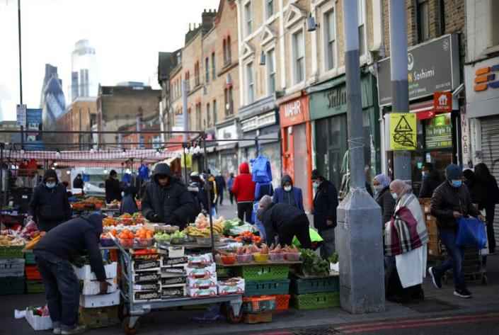 FILE PHOTO: People shop at a market stalls, amid the coronavirus disease (COVID-19) outbreak, in east London