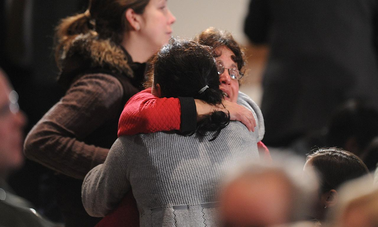 NEWTOWN, CT - DECEMBER 16:  Mourners comfort one another before U.S. President Barack Obama speaks at an interfaith vigil for the shooting victims from Sandy Hook Elementary School on December 16, 2012 at Newtown High School in Newtown, Connecticut. Twenty-six people were shot dead, including twenty children, after a gunman identified as Adam Lanza opened fire at Sandy Hook Elementary School. Lanza also reportedly had committed suicide at the scene. A 28th person, believed to be Nancy Lanza, found dead in a house in town, was also believed to have been shot by Adam Lanza. (Photo by Olivier Douliery-Pool/Getty Images)