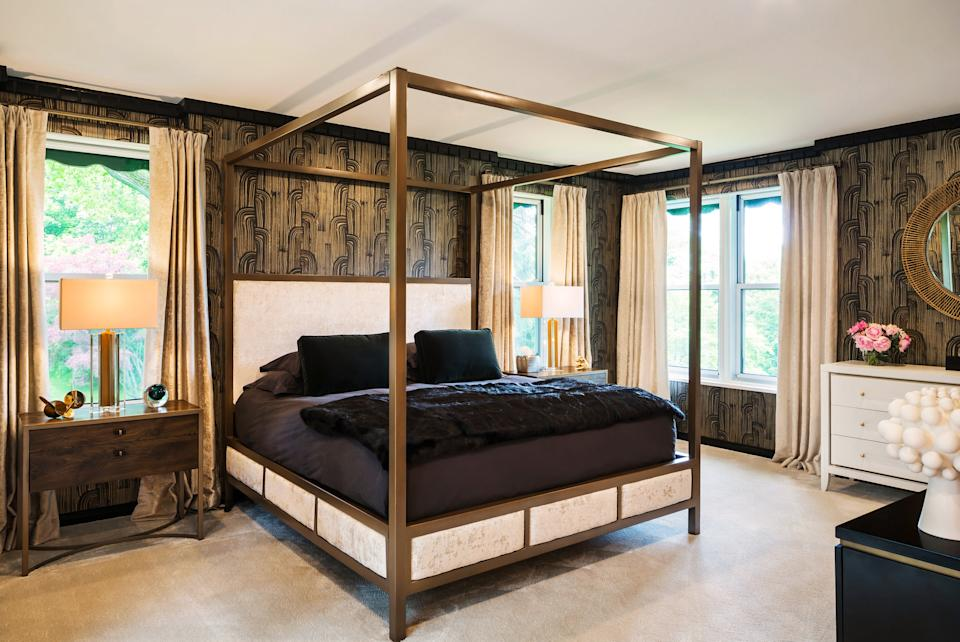 """<div class=""""caption""""> """"The mandate for the [main] bedroom was that they wanted to go in a much more adult and glam direction,"""" says McLeod. The designer kept the original millwork trim, painted it black, and used it as the launching point for the rest of the design. She chose a black-and-gold Kelly Wearstler for <a href=""""https://www.kravet.com/fabric"""" rel=""""nofollow noopener"""" target=""""_blank"""" data-ylk=""""slk:Lee Jofa"""" class=""""link rapid-noclick-resp"""">Lee Jofa</a> wallpaper and paired it with a custom-designed bed with <a href=""""https://www.kravet.com/fabric"""" rel=""""nofollow noopener"""" target=""""_blank"""" data-ylk=""""slk:Kravet"""" class=""""link rapid-noclick-resp"""">Kravet</a> fabric. The bedlinens are from <a href=""""https://www.restorationhardware.com/"""" rel=""""nofollow noopener"""" target=""""_blank"""" data-ylk=""""slk:RH"""" class=""""link rapid-noclick-resp"""">RH</a>, the bedside tables are from <a href=""""https://caracole.com/"""" rel=""""nofollow noopener"""" target=""""_blank"""" data-ylk=""""slk:Caracole"""" class=""""link rapid-noclick-resp"""">Caracole</a>, and the lamps are <a href=""""https://www.curreyandcompany.com/"""" rel=""""nofollow noopener"""" target=""""_blank"""" data-ylk=""""slk:Currey & Co"""" class=""""link rapid-noclick-resp"""">Currey & Co</a>. </div>"""