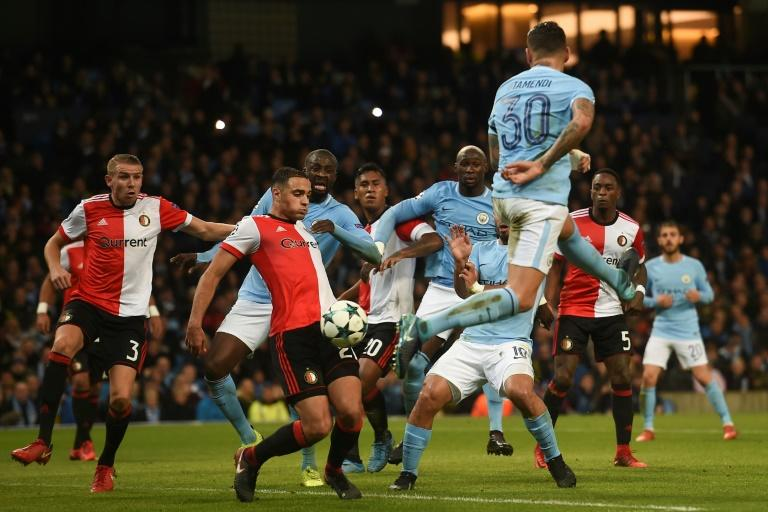 Feyenoord's midfielder Sofyan Amrabat (L) takes the ball on his knee after it clears Manchester City's defender Nicolas Otamendi (R) during the UEFA Champions League Group F football match November 21, 2017