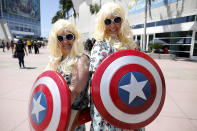 <p>Texans Cathrine Morgan and Trudy Alison wear blond wigs as they pose with shields at Comic-Con International on July 19, 2018, in San Diego. (Photo: Gregory Bull/AP) </p>