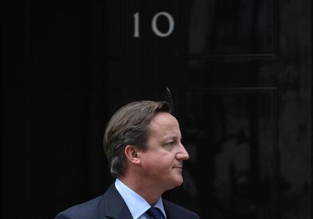 Britain's PM Cameron waits to meet Palestinian President Abbas outside of 10 Downing Street in London