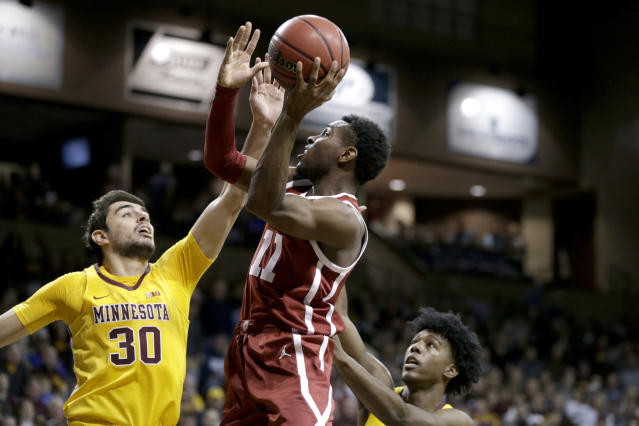 Oklahoma's De'Vion Harmon (11) shoots against Minnesota's Alihan Demir (30) and Marcus Carr, right, during the first half of an NCAA college basketball game in Sioux Falls, S.D., Saturday, Nov. 9, 2019. (AP Photo/Nati Harnik)