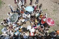 Hunger: People in the Tigrayan village of Baker wait for food being distributed on Sunday by the Amhara government