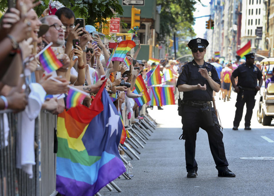 FILE - A police officer applauds as parade-goers shout and wave flags during the New York City Pride Parade, Sunday, June 26, 2016 in New York. As Pride weekend approaches, the recent decision by organizers of New York City's event to ban LGBTQ police officers from marching in future parades while wearing their uniforms has put a spotlight on issues of identity and belonging, power and marginalization. (AP Photo/Mel Evans, File)