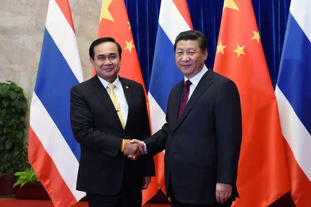 Thailand's Prime Minister Prayuth Chan-ocha shakes hands with China's President Xi Jinping before a meeting at the Great Hall of the People in Beijing