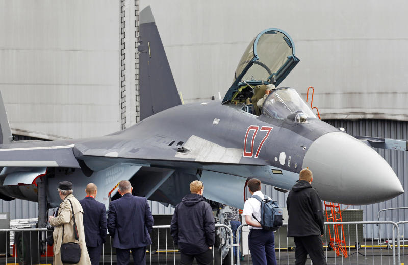 Visitors watch a Sukhoi SU-35 made by United Aircraft Corporation, displayed at the 50th Paris Air Show at Le Bourget airport, north of Paris, Thursday June 20, 2013. (AP Photo/Remy de la Mauviniere)