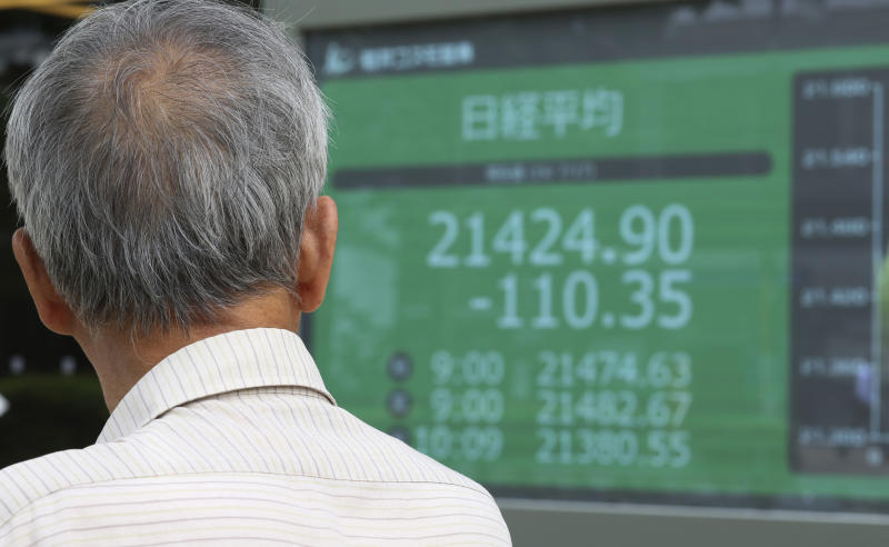 A man looks at an electronic stock board of a securities firm in Tokyo, Wednesday, July 17, 2019. Asian stocks were mixed Wednesday as Wall Street ended a five-day winning streak after the first big round of corporate earnings reports. (AP Photo/Koji Sasahara)