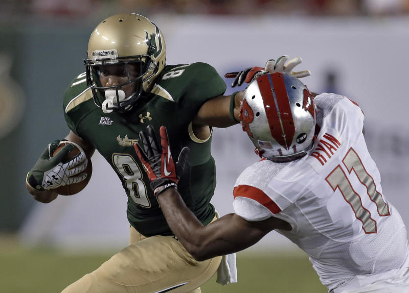South Florida wide receiver Andre Davis (81) stiff-arms Rutgers defensive back Logan Ryan (11) after a reception during the first quarter of an NCAA college football game Thursday, Sept. 13, 2012, in Tampa, Fla. (AP Photo/Chris O'Meara)