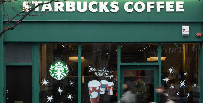 "Pedestrians walk past a branch of the Starbucks cafe chain in west London, Monday, Dec. 3, 2012. A committee of British lawmakers says the government should ""get a grip"" and clamp down on multinational corporations that exploit tax laws to move profits generated in Britain to offshore domains.The committee says major multinationals including Starbucks, Google and Amazon are guilty of immoral tax avoidance. Starbucks announced it is reviewing its British tax practices in a bid to restore public trust. (AP Photo/Alastair Grant)"