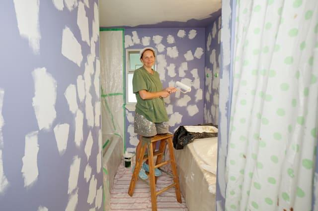 Woman in spotted bathroom painting the walls.