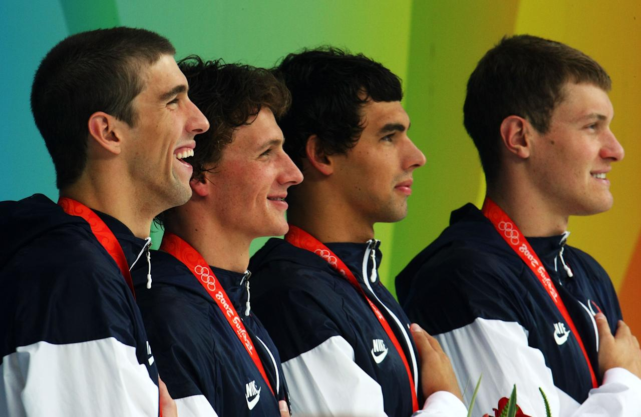 BEIJING - AUGUST 13:  (L-R) Michael Phelps, Ryan Lochte, Ricky Berens and Peter Vanderkaay of the United States pose with the gold medal on the podium during the medal ceremony for the Men's 4 x 200m Freestyle Relay Final at the National Aquatics Centre during Day 5 of the Beijing 2008 Olympic Games on August 13, 2008 in Beijing, China.  The United States won the race in a time of 6:58.56, a new World Record.  (Photo by Alexander Hassenstein/Getty Images)