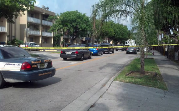 Police cars line a street where a seven were killed at an apartment building in Hialeah, Fla., early Saturday, July 27, 2013. A gunman holding hostages inside the apartment complex killed six people before being shot to death by a SWAT team that stormed the building early Saturday following an hours-long standoff, police said. (AP Photo/The Miami Herald, Joey Flechas)