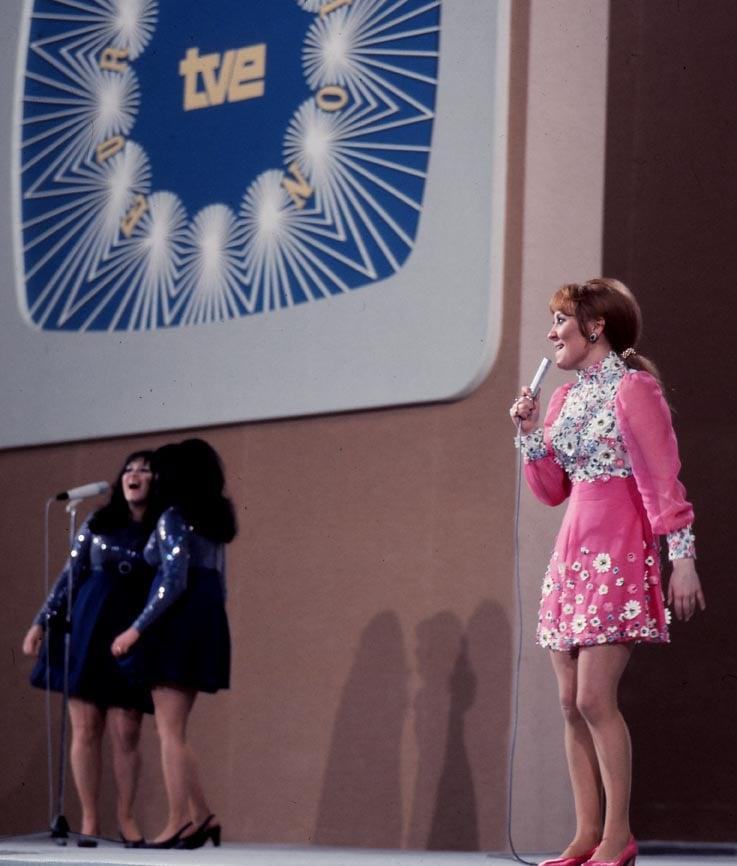 """<p>Before representing the UK in the 1969 Eurovision contest, Lulu had a burgeoning career as a pop singer and actress. Her controversial co-win (she was one of four winners in an unprecedented four-way tie) only raised her profile further. She went on to sing <a href=""""https://www.popsugar.com/entertainment/best-james-bond-movie-theme-songs-47106119"""" class=""""ga-track"""" data-ga-category=""""Related"""" data-ga-label=""""http://www.popsugar.com/entertainment/best-james-bond-movie-theme-songs-47106119"""" data-ga-action=""""In-Line Links"""">a Bond theme song</a> for <strong>The Man with the Golden Arm</strong> and was nominated for a Grammy in 1982.</p>"""