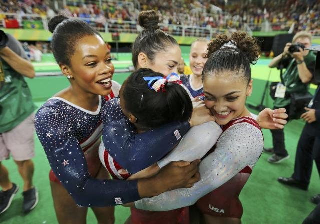 2016 Rio Olympics - Artistic Gymnastics - Final - Women's Team Final - Rio Olympic Arena - Rio de Janeiro, Brazil - 09/08/2016. Simone Biles (USA) of USA (back-facing camera) is hugged by team mates (from L) Gabrielle Douglas (USA) of USA (Gabby Douglas), Alexandra Raisman (USA) of USA (Aly Raisman), Madison Kocian (USA) of USA and Laurie Hernandez (USA) of USA following her floor routine during the women's team final. Team USA won gold in the event. REUTERS/Mike Blake TPX IMAGES OF THE DAY. FOR EDITORIAL USE ONLY. NOT FOR SALE FOR MARKETING OR ADVERTISING CAMPAIGNS.