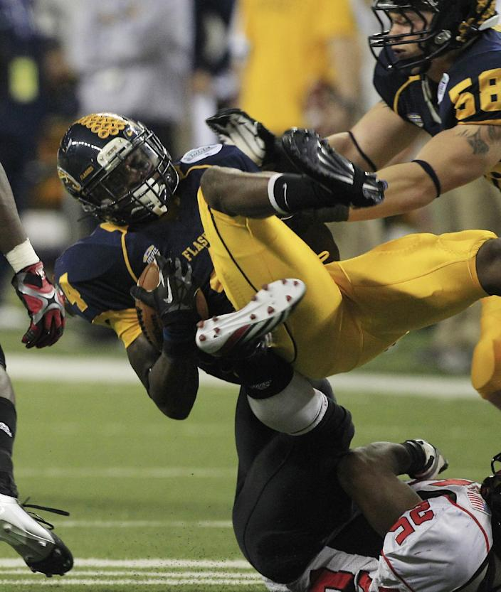 Kent State wide receiver Eric Adeyemi (4) is upended by Northern Illinois' Giorgio Bowers (25) during the third quarter of the Mid-American Conference championship NCAA college football game on Friday, Nov. 30, 2012. (AP Photo/Carlos Osorio)