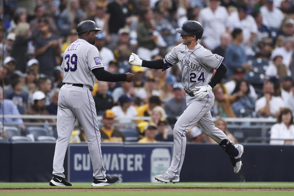 Colorado Rockies' Ryan McMahon, right, is congratulated by third base coach Stu Cole after hitting a grand slam against the San Diego Padres during the first inning of a baseball game Friday, July 30, 2021, in San Diego. (AP Photo/Derrick Tuskan)