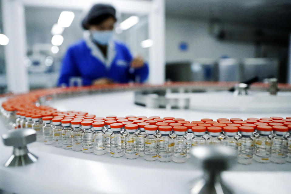 FILE - In this Dec. 23, 2020, file photo released by China's Xinhua News Agency, a Sinovac worker checks the labeling on vials of COVID-19 vaccines on a packaging line in Beijing. With just four of China's many vaccine makers claiming they are able to produce at least 2.6 billion doses this year, a large part of the world's population will end up inoculated not with Western vaccines boasting headline-grabbing efficacy rates, but with China's traditionally made shots. (Zhang Yuwei/Xinhua via AP, File)