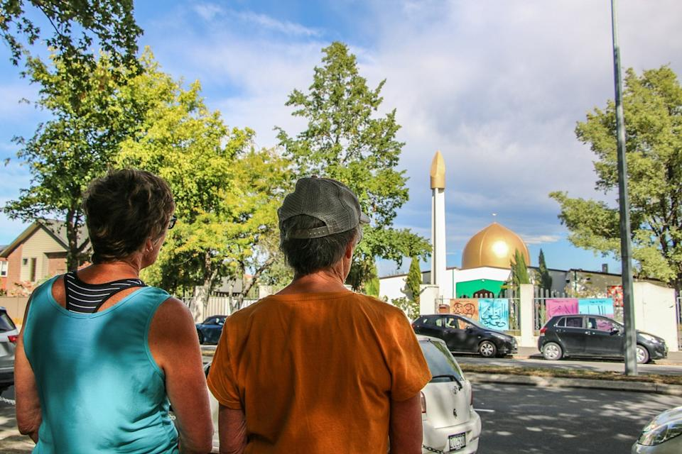 Two tourists in Christchurch stand opposite the Al Noor Mosque, the site of the 2019 attacks that killed 51 worshippers. (Photo by Adam Bradley/SOPA Images/LightRocket via Getty Images)