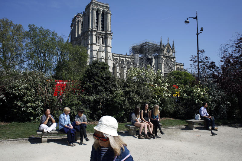 People sit in a park near Notre Dame cathedral, in Paris, Friday, April 19, 2019. Rebuilding Notre Dame, the 800-year-old Paris cathedral devastated by fire this week, will cost billions of dollars as architects, historians and artisans work to preserve the medieval landmark. (AP Photo/Thibault Camus)