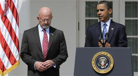 Retired General James Clapper stands next to President Barack Obama in the Rose Garden at the White House in Washington