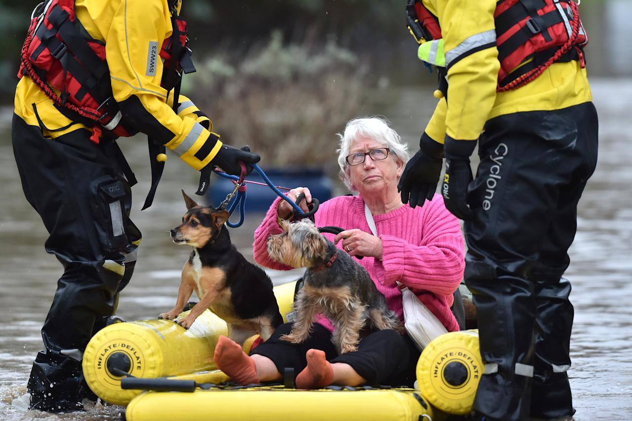 A woman and her two dogs are rescued from the floods. (PA)