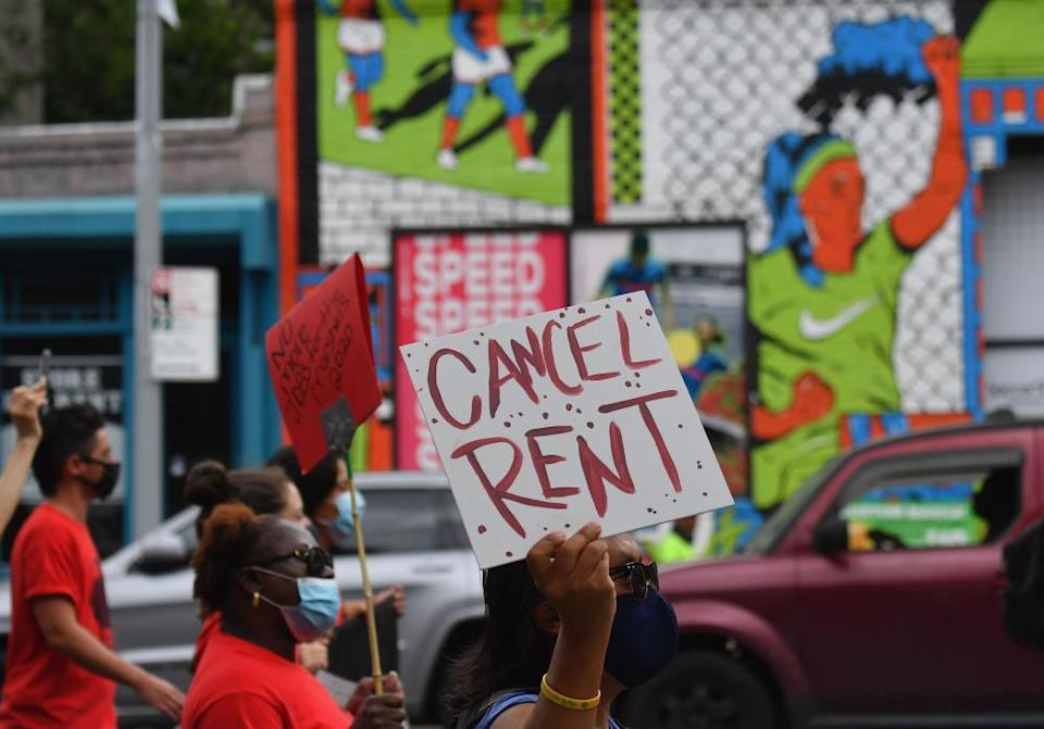 Protesters hold signs calling for rent to be cancelled.