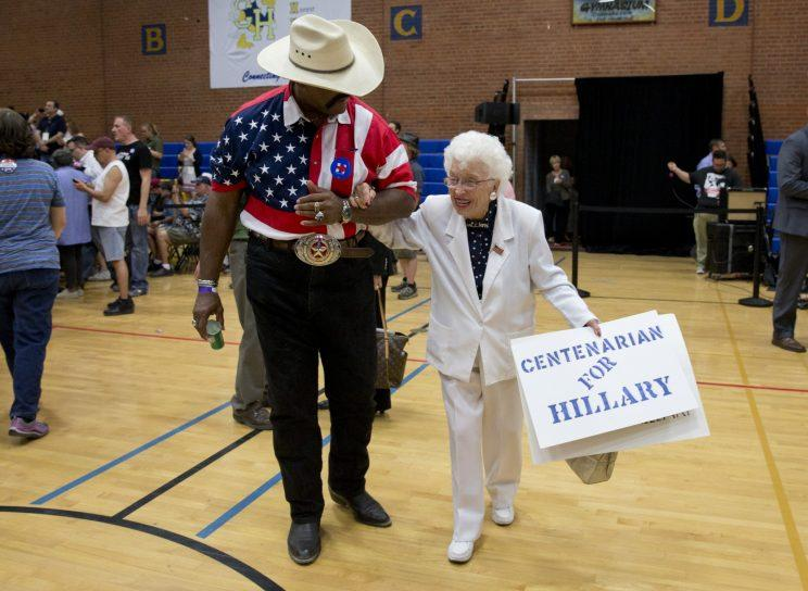 John Goodie escorts Jerry Emmett, a Democratic presidential candidate Hillary Clinton supporter, to her seat before Clinton arrives to speak at a campaign event at Carl Hayden Community High School in Phoenix, Monday, March 21, 2016.
