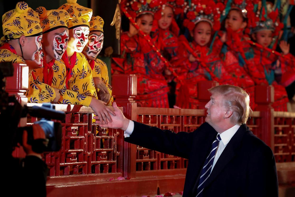 President Donald Trump shakes hands with opera performers at the Forbidden City.