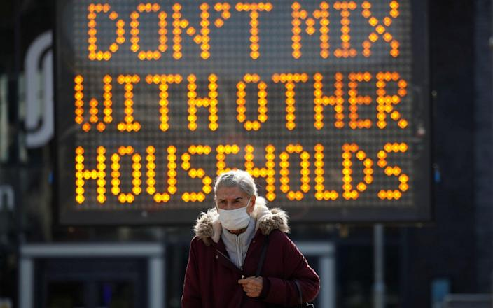 A woman out walking in Bolton as the 'rule of six' came into force - Phil Noble/Reuters