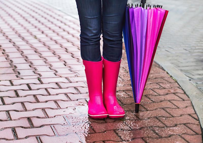 Autumn. Protection in the rain. Woman (girl) wearing pink rubber boots and has colorful umbrella. Street, city. Raindrops. Copy space. Place for message. Outdoor Concept about activity, leisure, travel.
