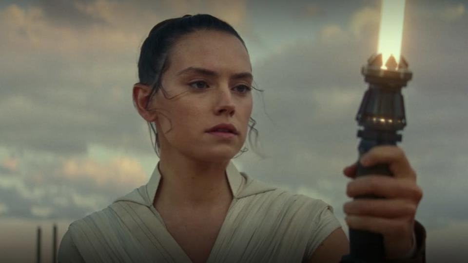 Daisy Ridley looks at her yellow lightsaber in The Rise of Skywalker