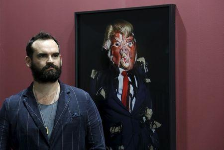 """British artist James Ostrer poses beside a photo taken by him of his creation entitled """"Emotional Download"""" during an art exhibition in Hong Kong"""