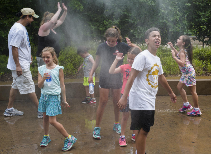 FILE - In this July 11, 2017 file photo, visitors to the Henry Doorly Zoo in Omaha, Neb. cool off at a misting station as temperatures reach 95 degrees Fahrenheit and the humid air makes it feel like 105 degrees. Earth sizzled to yet another all-time heat record last month. The National Oceanic and Atmospheric Administration said Thursday that Earth's land surfaces in July were the hottest since record keeping began in 1880. (AP Photo/Nati Harnik, File)