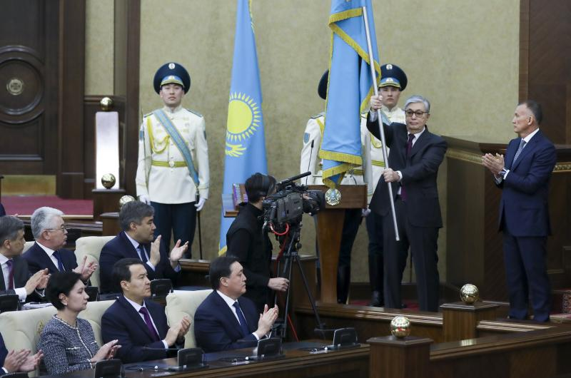 Kazakhstan's interim president Kassym-Jomart Tokayev, second right, holds a national flag during an inauguration ceremony in Astana, Kazakhstan, Wednesday, March 20, 2019. The speaker of Kazakhstan's parliament was sworn as interim president on Wednesday, a day after longtime leader Nursultan Nazarbayev abruptly resigned. (AP Photo)