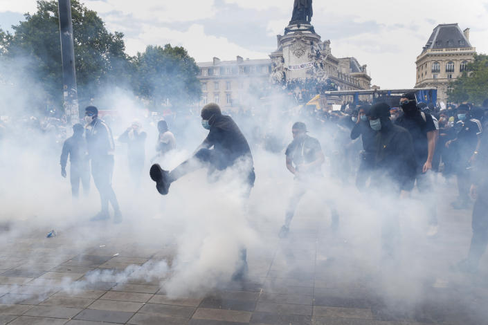 A man kicks a tear gas canister during a march against police brutality and racism in Paris, France, Saturday, June 13, 2020, organized by supporters of Adama Traore, who died in police custody in 2016 in circumstances that remain unclear despite four years of back-and-forth autopsies. The march is expected to be the biggest of several demonstrations Saturday inspired by the Black Lives Matter movement in the U.S., and French police ordered the closure of freshly reopened restaurants and shops along the route fearing possible violence. (AP Photo/Thibault Camus)