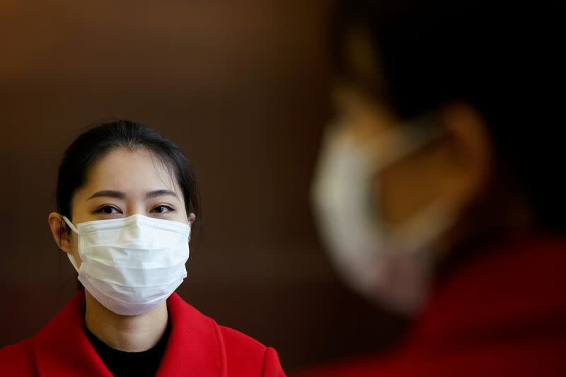 Staff members wearing face masks are seen at an entrance of a shopping mall in Wuhan