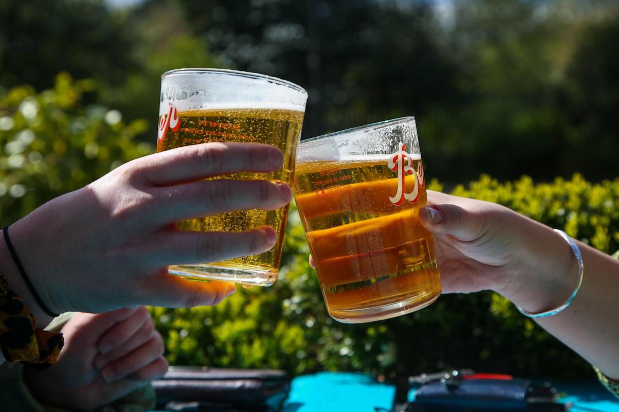 LONDON, UNITED KINGDOM - 2021/04/12: A couple raises their pints of beer on a warm sunny morning in a beer garden of a pub in London. According to the Met Office, warm weather is forecasted for the next few days in the south east of England. (Photo by Dinendra Haria/SOPA Images/LightRocket via Getty Images)