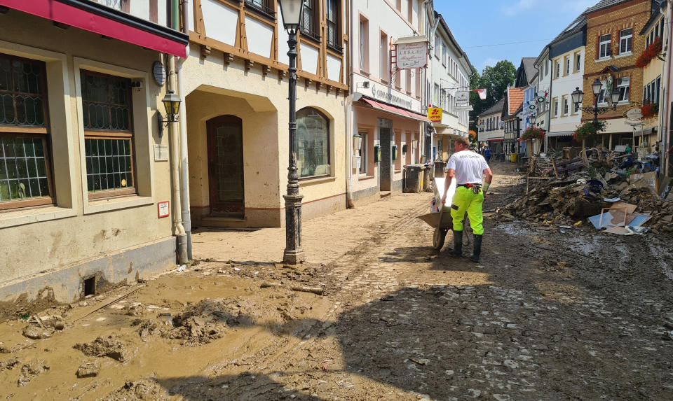 A man uses a wheelbarrow to move debris through the streets of the flood hit town of Ahrweiler, Germany, on Friday, July 23, 2021. With the death toll and economic damage from last week's floods in Germany continuing to rise, questions have been raised about why systems designed to warn people of the impending disaster didn't work. (AP Photo/Frank Jordans)