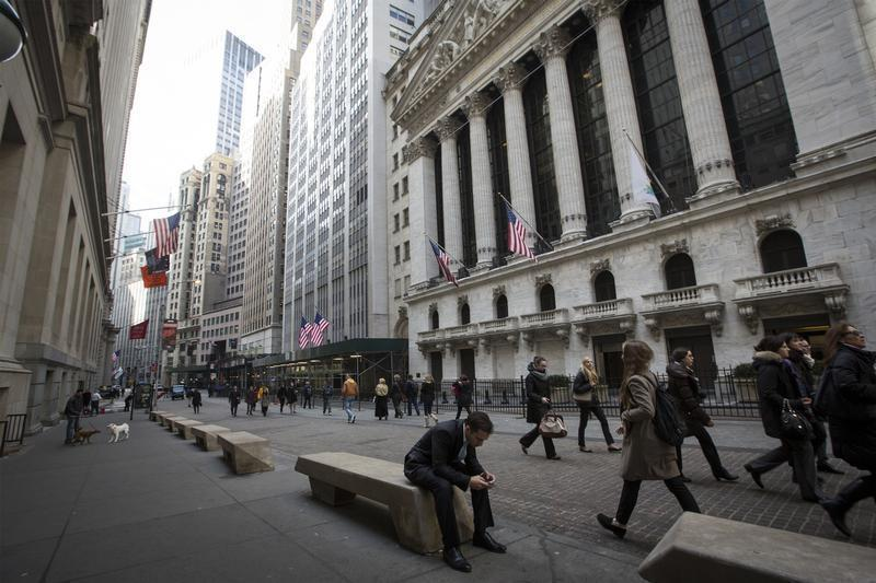 People walk by the New York Stock Exchange in New York's financial district
