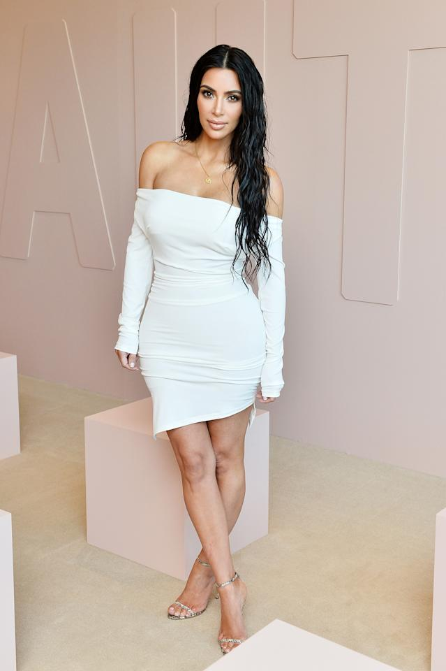 <p>In a Vivienne Westwood off-the-shoulder white mini dress and simple heels at the launch of her KKW Beauty products. </p>