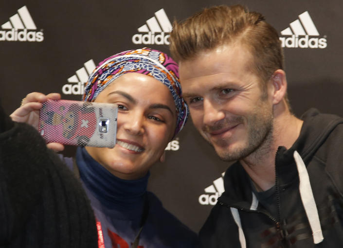 """File - In this Thursday, Feb. 28, 2013, file photo Paris Saint Germain's David Beckham poses for a photograph with unidentified fan during a media event, in a sports store, on the Champs Elysees Avenue, in Paris. Selfie"""" the smartphone self-portrait has been declared word of the year for 2013 by Britain's Oxford University Press. (AP Photo/Francois Mori, File)"""