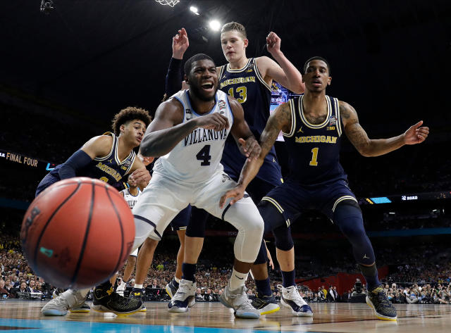 Villanova's Eric Paschall (4) reacts as he loses the control of the ball against Michigan's Moritz Wagner (13) and Charles Matthews (1) during the first half in the championship game of the Final Four NCAA college basketball tournament, Monday, April 2, 2018, in San Antonio. (AP Photo/Eric Gay)