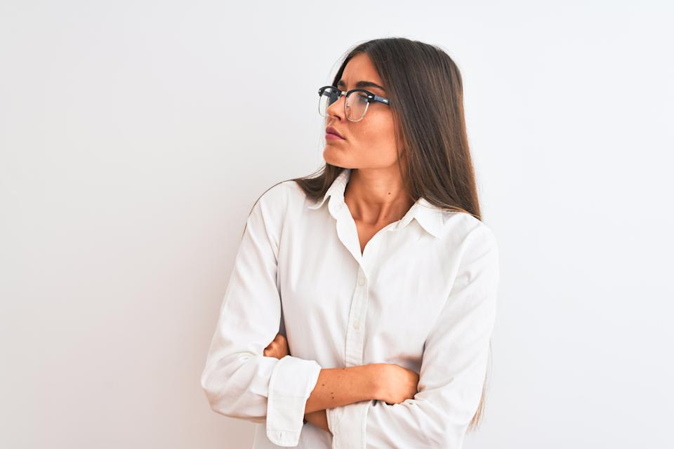 Young beautiful businesswoman wearing glasses standing over isolated white background looking to the side with arms crossed convinced and confident
