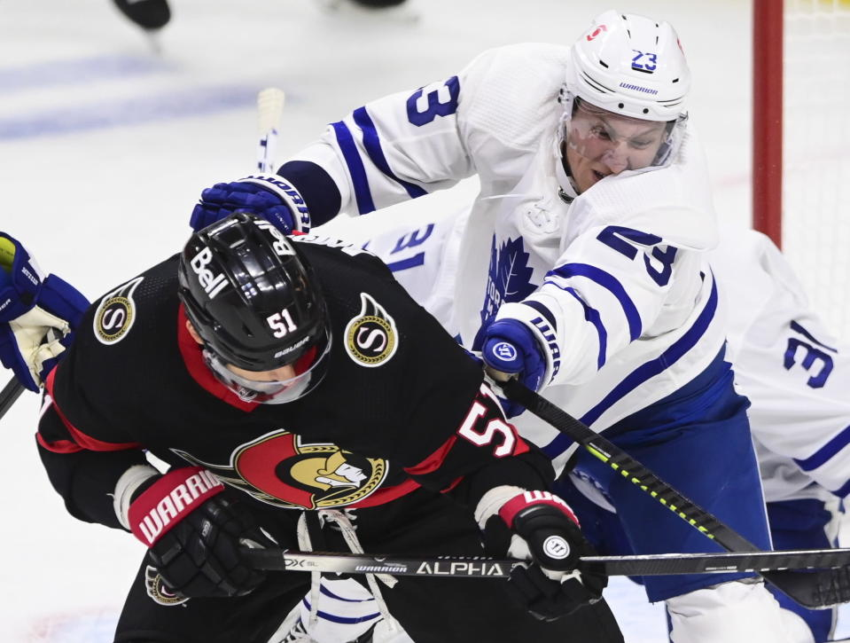 Toronto Maple Leafs defenseman Travis Dermott (23) defends against Ottawa Senators center Artem Anisimov (51) during the first period of an NHL hockey game Friday, Jan. 15, 2021, in Ottawa, Ontario. (Sean Kilpatrick/The Canadian Press via AP)