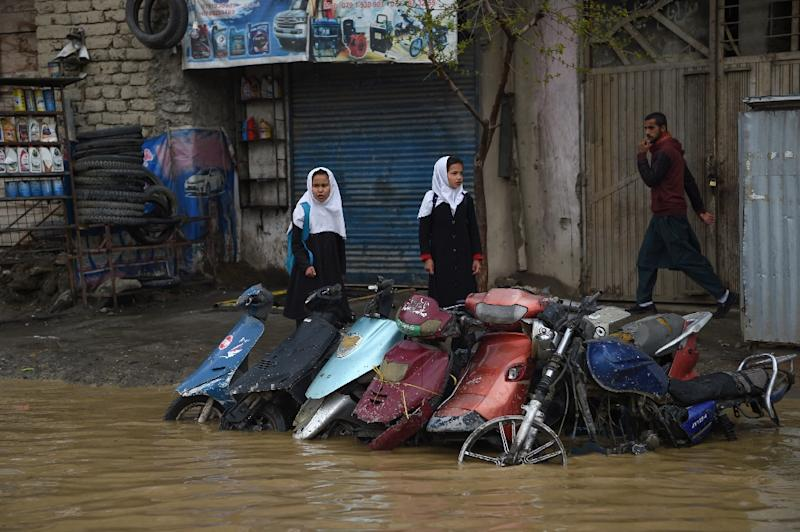 Pedestrians look for dry ground on a street after heavy rains in Kabul (AFP Photo/WAKIL KOHSAR)